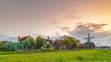 Evening street view on typically traditional Dutch house, windmill, historical architecture and bridge at the Zaanse Schans, Popular touristic landmark.
