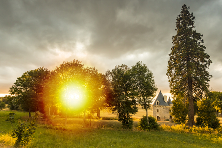 A small, hidden, pitoresk castle during a beautiful sunset on a dreamlike landscape on farmland. Stock Photo