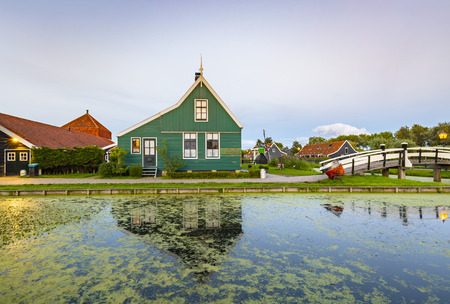 Typically traditional Dutch house, windmill, historical architecture and bridge over water at the Zaanse Schans, Popular touristic landmark.