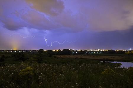 Intracloud lightning thunderbolt IC strikes at night above a city. Dramatic cloudscape thunderstorm, hills with flowers on the foreground, city on the background