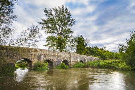 Puente medieval de piedra vieja sobre un río que fluye en Inglaterra. Cloudscape dramático y tonos de colores antiguos