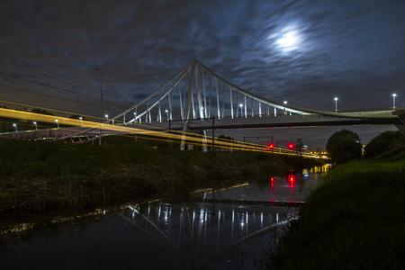 Pont suspendu la nuit au clair de lune avec des traînées lumineuses de voitures en mouvement et de trains d'autoroute et de chemin de fer en dessous