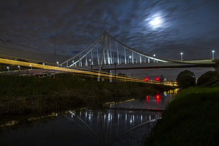 Suspension bridge at night under moonlight with light trails of moving cars and trains of highway and railway underneath