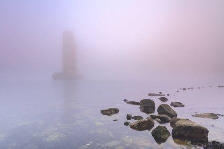 Een van de overgebleven pijlers van de stormvloedkering staat in het water tijdens een zware, dichte mistige winterzonsondergang bij de delta werkt stormvloedkering zeewering Neeltje Jans in Zeeland, Nederland