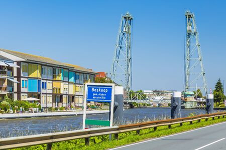 City name sign in front of contemporary style houses and vertical lift bridge crossing the river Gouwe at the picturesque village Boskoop, the Netherlands.