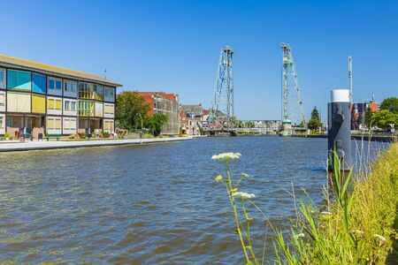 View over water at contemporary style houses and a vertical lift bridge crossing the river Gouwe at the picturesque village Boskoop, the Netherlands, famous for its plant nurseries Stockfoto