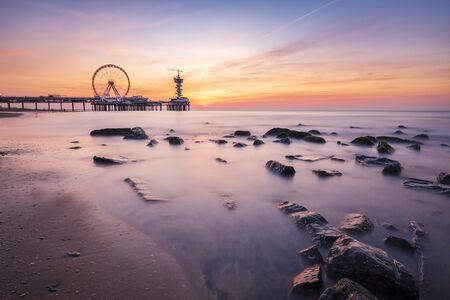 Colorful sunset on coastline, beach, pier and ferris wheel, Scheveningen, the Hague.
