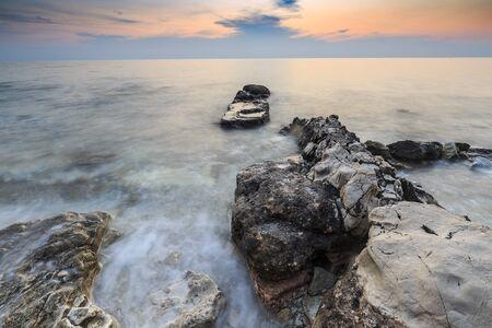 Colorful sunset on a beach with rocks on the Adriatic Sea coast Istria Croatia Фото со стока - 132062793