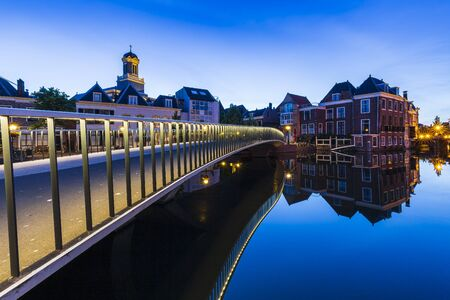 Traditional Dutch culture architecture houses and canal during the blue hour. Historical and touristic town Leiden, the Netherlands Фото со стока - 132062576