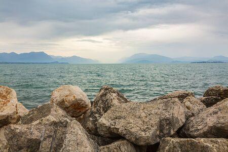 Bad weather and dark clouds over lake Garda and mountain landscape, Desenzano, Brescia, Lombardy, Italy. Фото со стока - 133512705