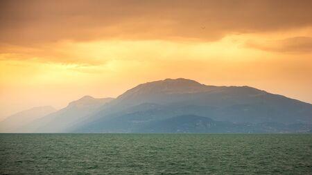 Beautiful sunset clouds over lake Garda and mountain landscape, Desenzano, Brescia, Lombardy, Italy.