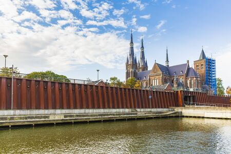 Floodwall at the river Meuse protecting the small village Cuijk, the Netherlands. Sunny day in Autumn season