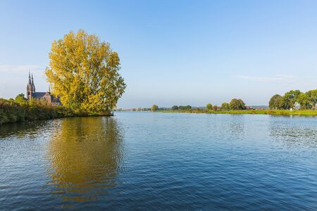 Land van Cuijk, agricultural landscape at the small village Cuijk and the Meuse river, the Netherlands under a blue sky. Popular touristic landmark for travel Фото со стока - 133512715