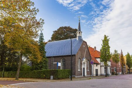 Small church and residential houses in a street in the small village Cuijk, the Netherlands. Autumn season, beautiful sunlight. Фото со стока