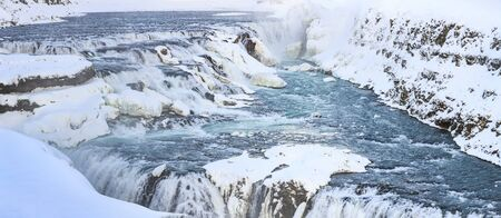 Gullfoss waterfalls located along the golden circle route, Iceland during Winter season. Ice, snow, water and sunset. Фото со стока