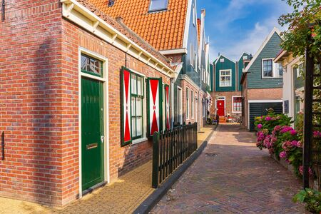 Old streets in Volendam. Old traditional fishing village, typical wooden houses architecture. Popular landmark and travel destination for tourists.