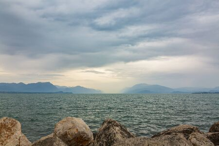Bad weather and dark clouds over lake Garda and mountain landscape, Desenzano, Brescia, Lombardy, Italy.