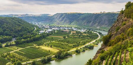 View at a steel beam bridge connecting the Hunsrück and Eifel mountain ranges looking over the Moselle river and Winningen vineyards wine region.
