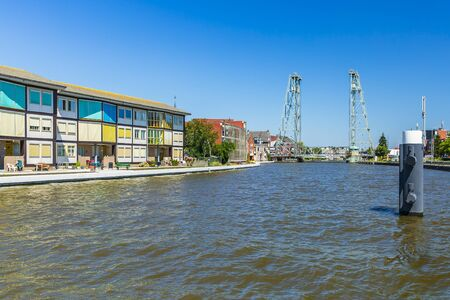 View over water at contemporary style houses and a vertical lift bridge crossing the river Gouwe at the picturesque village Boskoop, the Netherlands, famous for its plant nurseries Stock Photo