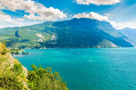 Aerial view at the popular touristic villages Linfano and Torbole at northern lake Garda, Italy. on a beautiful summer day. Blue water, rocks, mountains, sunlight and clear sky.