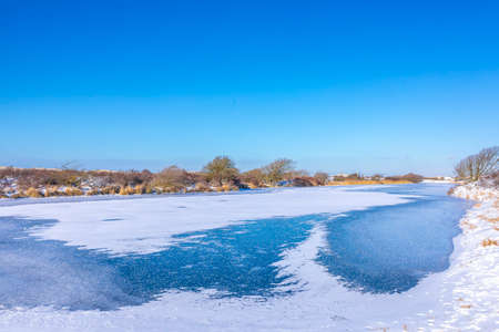 Snowy and ice winter landscape at the Amsterdamse Waterleidingduinen, clear blue sky.