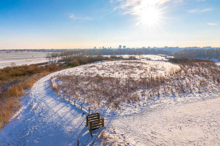 Snowy landscape with hills and meadows under a blue sky in Winter season. Buytenpark Zoetermeer, the Netherlands Stock Photo
