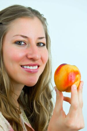 charmingly: charmingly smiling girl showing a fresh peach Stock Photo