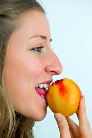 sweetly: sweetly smiling girl eating a peach Stock Photo