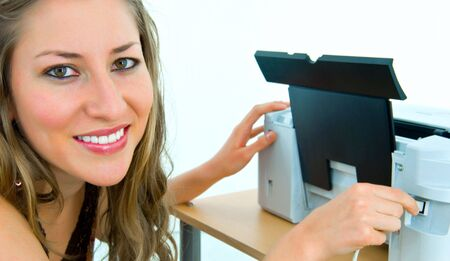 pretty office girl inserting a cable into a printer port photo