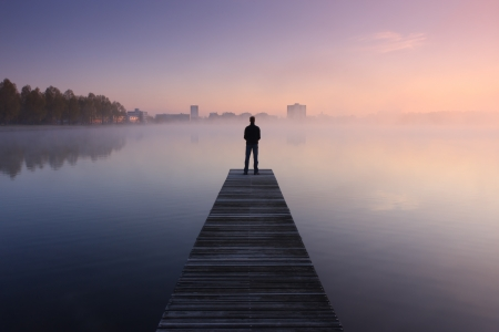 man standing alone: Man standing on a jetty looking at a city over foggy water at dawn
