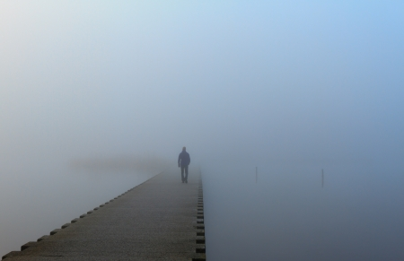Man walking on a pier in the fog