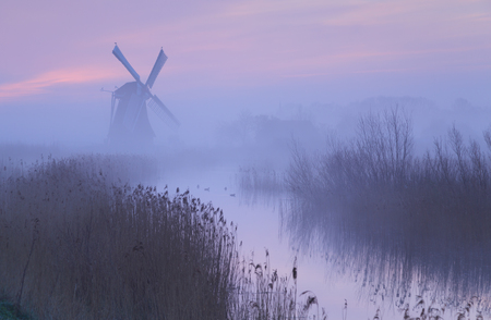 watermanagement: Foggy, pink sunrise in Holland with a traditional windmill in the wetlands. Stock Photo