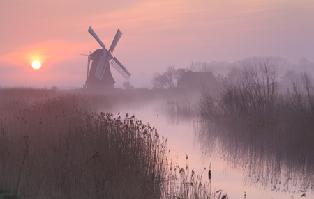 traditional windmill: Foggy, pink sunrise in Holland with a traditional windmill in the wetlands. Stock Photo