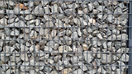 gabion mesh: Close up of protective gabions, broken stones behind grid