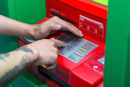 automatic transaction machine: Persona que usa la máquina de caché del teclado para retirar dinero