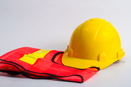 Yellow hard hat and orange and yellow reflective best over white background