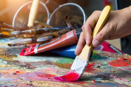 artist paints a picture of oil paint brush in hand with palette closeup Stock Photo
