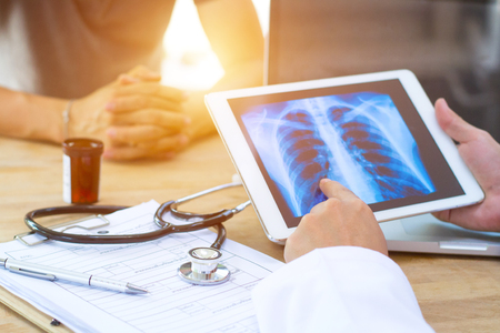 Doctor shows results to old patient x-ray of the lungs, smoking cigarettes problem Standard-Bild