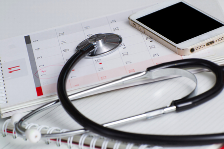 定期健康診断の概念、カレンダー上の聴診器 写真素材