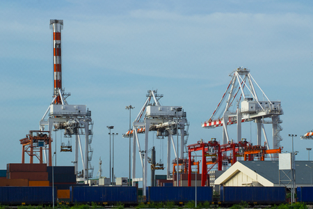 Container Cargo freight with working crane bridge in shipyard at dusk for Logistic Import Export background