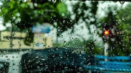 Rain drops fall on the windshield.