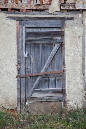 door bolt: old wooden door locked with a rusty iron bolt Stock Photo