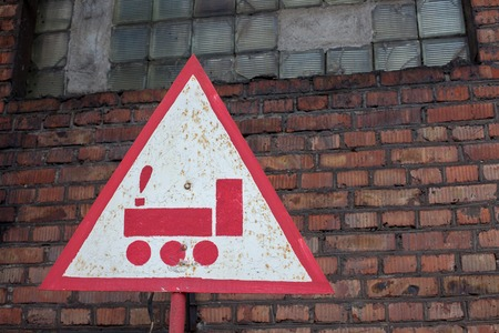 brick road: road sign train on a background of red brick wall