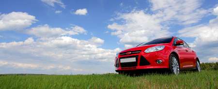 red car on the green grass against the sky Foto de archivo