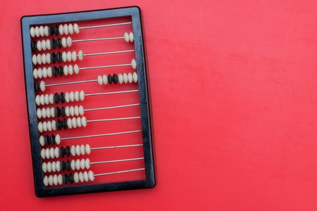 ancient abacus with knuckles on a red background