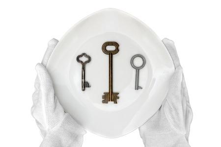 Three metal keys on a white plate. Reklamní fotografie