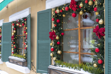 windows are decorated with branches of fir and Christmas tinsel.