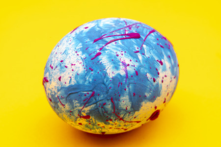 Blue handmade Easter egg on a yellow background. Religious traditional holiday. Stock Photo