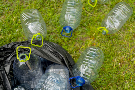 Plastic bottles in a black plastic trash bag on a grass background.