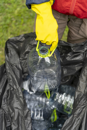 Separate garbage collection. Hand putting plastic bottle into black plastic trash bag filled with other bottles.